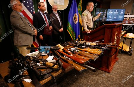 Los Angeles County Sheriff Alex Villanueva, right, with Tom Lackey, California State Assembly Member, U.S Representative Mike Garcia, and City of Lancaster Mayor Rex Parris, left to right, stand by the display of some of the weapons seized as they and other officials discuss the results of the largest Marijuana Eradication Operation of illegal Marijuana cultivations in the history of the Los Angeles County Sheriff's Department that resulted in the seizure of approximately 373,000 marijuana plants and 33,480 lbs of harvested marijuana worth about $1.193 billion dollars. Hall of Justice on Wednesday, July 7, 2021 in Los Angeles, CA. (Al Seib / Los Angeles Times).