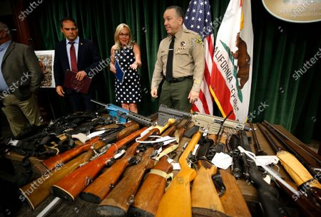 Los Angeles County Sheriff Alex Villanueva, right, with Supervisor Kathryn Barger, Los Angeles County Board of Supervisors, and U.S Representative Mike Garcia, left, react to the display of some of the weapons seized as he and other officials discuss the results of the largest Marijuana Eradication Operation of illegal Marijuana cultivations in the history of the Los Angeles County Sheriff's Department that resulted in the seizure of approximately 373,000 marijuana plants and 33,480 lbs of harvested marijuana worth about $1.193 billion dollars. Hall of Justice on Wednesday, July 7, 2021 in Los Angeles, CA. (Al Seib / Los Angeles Times).