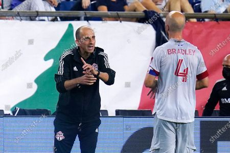 Toronto FC interim coach Javier Perez talks with midfielder Michael Bradley during the first half of an MLS soccer match against the New England Revolution, in Foxborough, Mass