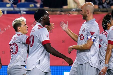 Stock Picture of Toronto FC midfielder Yeferson Soteldo, left, is congratulated by midfielder Michael Bradley, right, after his goal in the first half of an MLS soccer match against the New England Revolution, in Foxborough, Mass. At center is Toronto FC forward Ayo Akinola