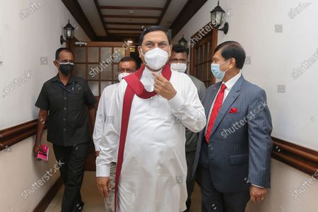 Stock Photo of Basil Rohana Rajapaksa (C), arrives to assume duties as Sri Lanka's new Minister of Finance at the ministry office in Colombo, Sri Lanka, 08 July 2021. Basil Rajapaksa, brother of President Gotabaya Rajapaksa and Prime Minister Mahinda Rajapaksa, enters Parliament as the sixth member of the Rajapaksa family in the 9th parliament and the fourth member of the Rajapaksa Brothers. Entered Parliament through the national list system Basil Rajapaksa was sworn in as the new Minister of Finance in Sri Lanka. The Indian Ocean island nation's Powerful Rajapaksa brothers won the landslide victory during the 2020 August parliamentary election and secured the 145 majority seats out of 225 seats in the parliament of Sri Lanka.