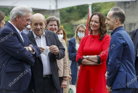 (L-R) Luxembourg's Foreign Minister Jean Asselborn, French Foreign Minister Jean-Yves Le Drian, German Foreign Minister's partner actress Natalia Woerner and German Foreign Minister Heiko Maas chat near the Monument 'Schengen Agreement', prior to an informal meeting in Schengen, Luxembourg, 08 July 2021. The informal meeting in Schengen will allow the foreign ministers to discuss several topics of common interest.