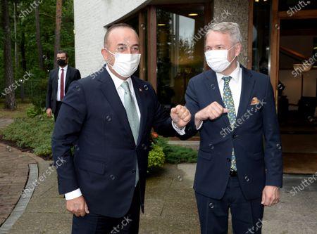 Finnish Foreign Minister Pekka Haavisto (R) welcomes his Turkish counterpart Mevlut Cavusoglu as they meet in Helsinki, Finland, on July 8, 2021.
