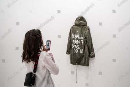 """Stock Image of Visitor takes a snapshot of an art work called """"Saponified Jacket of Melania Trump"""" by artist Sejia Kameric at the ARCO International Art Fair in Madrid, Spain"""