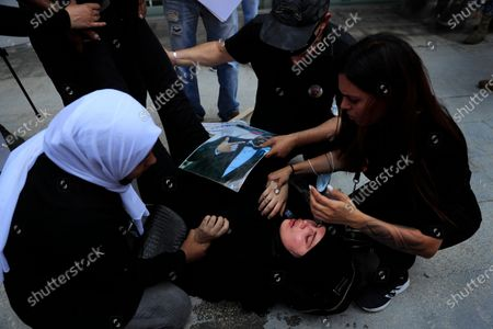 Families of the victims of last year's massive blast at Beirut's seaport, treat a woman who fell down while she was trying with others to reach the tightly-secured residents of parliament speaker Nabih Berri and was pushed back by Lebanese army soldiers, in Beirut, Lebanon, . The protest came after last week's decision by the judge to pursue senior politicians and former and current security chiefs in the case, and requested permission for their prosecution