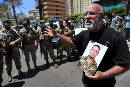 Father of a Lebanese army soldier who killed during the last year's massive blast at Beirut's seaport, holds his son's portrait and shouts slogans during a protest near the tightly-secured residents of parliament speaker Nabih Berri, in Beirut, Lebanon, . The protest came after last week's decision by the judge to pursue senior politicians and former and current security chiefs in the case, and requested permission for their prosecution