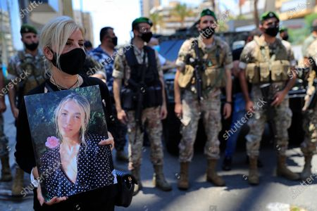 Woman holds a portrait of a victim who killed during the last year's massive blast at Beirut's seaport, protest near the tightly-secured residents of parliament speaker Nabih Berri, in Beirut, Lebanon, . The protest came after last week's decision by the judge to pursue senior politicians and former and current security chiefs in the case, and requested permission for their prosecution