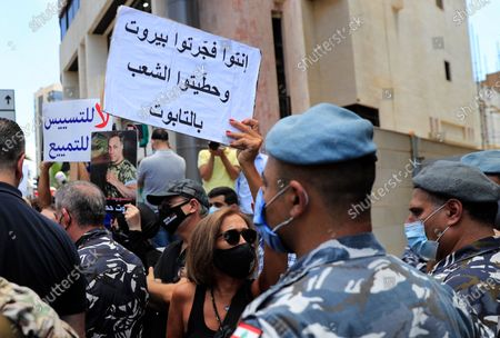 """Woman who lost her relative during the last year's massive blast at Beirut's seaport, holds an Arabic placard that reads:""""You exploded Beirut and you put the people in the coffin,"""" during a protest near the tightly-secured residents of parliament speaker Nabih Berri, in Beirut, Lebanon, . The protest came after last week's decision by the judge to pursue senior politicians and former and current security chiefs in the case, and requested permission for their prosecution"""