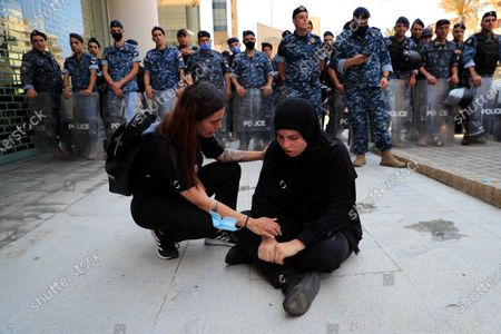Woman from the Families of the victims of last year's massive blast at Beirut's seaport, left, comforts a woman who fall down while she was trying with other to reach the tightly-secured residents of parliament speaker Nabih Berri and pushed back by Lebanese army soldiers, in Beirut, Lebanon, . The protest came after last week's decision by the judge to pursue senior politicians and former and current security chiefs in the case, and requested permission for their prosecution