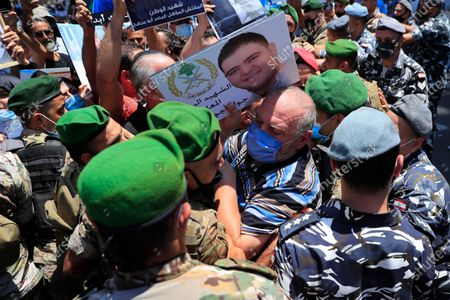 Father of a Lebanese army soldier who killed during the last year's massive blast at Beirut's seaport, holds his son's portrait as he pushed back by Lebanese army soldiers as he trying to reach the tightly-secured residents of parliament speaker Nabih Berri, in Beirut, Lebanon, . The protest came after last week's decision by the judge to pursue senior politicians and former and current security chiefs in the case, and requested permission for their prosecution
