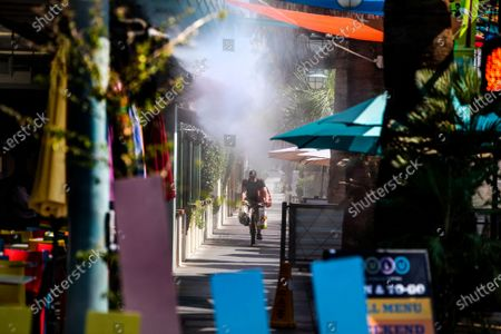 Stock Image of A bicyclist rides under cooling misters in 110 degree temperatures on July 8, 2021 in downtown Palm Springs, California. Another heat wave is expected this weekend in Southern California.(Gina Ferazzi / Los Angeles Times)