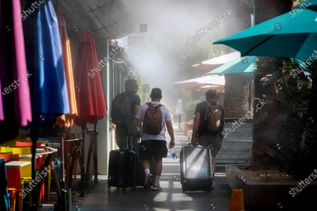 Stock Picture of Tourists pull their luggage under cooling misters in 110 degree temperatures on July 8, 2021 in downtown Palm Springs, California. Another heat wave is expected this weekend in Southern California.(Gina Ferazzi / Los Angeles Times)