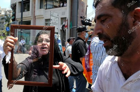 A woman holds a protrait of a deceased family member as soldiers block access to Ain al-Tineh Palace, the residence of the Parliament Speaker, in Beirut, Lebanon, 09 July 2021. Families of some victims of 04 August 2020 Beirut port explosion gathered to protest at the Ain al-Tineh palace where the Parliament's Administration and Justice Committee was meeting to debate on the immunity of three MPs to be investigated in the case of the Beirut port explosion. A massive blast on 04 August 2020 rocked Beirut's port in which at least 200 people were killed and more than 6,000 injured,  believed to have been caused by an estimated 2,750 tons of ammonium nitrate stored in a warehouse, devastated the port area of Beirut and several parts of the city.