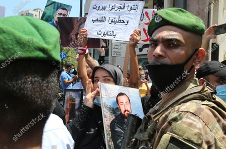 A woman holds a protrait of a deceased family member in front of soldiers blocking access to Ain al-Tineh Palace, the residence of the Parliament Speaker, in Beirut, Lebanon, 09 July 2021. Families of some victims of 04 August 2020 Beirut port explosion gathered to protest at the Ain al-Tineh palace where the Parliament's Administration and Justice Committee was meeting to debate on the immunity of three MPs to be investigated in the case of the Beirut port explosion. A massive blast on 04 August 2020 rocked Beirut's port in which at least 200 people were killed and more than 6,000 injured,  believed to have been caused by an estimated 2,750 tons of ammonium nitrate stored in a warehouse, devastated the port area of Beirut and several parts of the city.