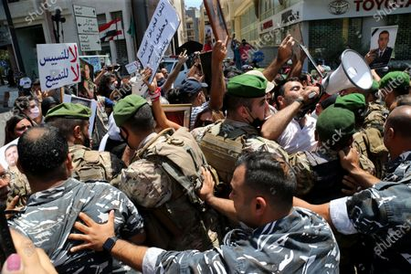 Stock Photo of Releatives of deceased family members protest as soldiers block access to Ain al-Tineh Palace, the residence of the Parliament Speaker, in Beirut, Lebanon, 09 July 2021. Families of some victims of 04 August 2020 Beirut port explosion gathered to protest at the Ain al-Tineh palace where the Parliament's Administration and Justice Committee was meeting to debate on the immunity of three MPs to be investigated in the case of the Beirut port explosion. A massive blast on 04 August 2020 rocked Beirut's port in which at least 200 people were killed and more than 6,000 injured,  believed to have been caused by an estimated 2,750 tons of ammonium nitrate stored in a warehouse, devastated the port area of Beirut and several parts of the city.
