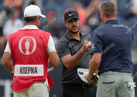 Brooks Koepka (USA) bumps fists with playing partner Jason Kokrak (USA) on the 18th green; Royal St Georges Golf Club, Sandwich, Kent, England; The Open Championship, PGA Tour, European Tour Golf, First Round .