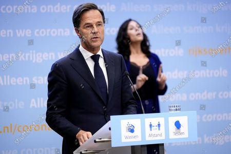 Dutch outgoing Prime Minister Mark Rutte (L) and a sign interpreter during an extra press conference in the Hague, The Netherlands, 09 July 2021. The cabinet takes measures to deal with the sharp increase in the number of positive corona infections.