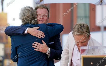 Television producer Nigel Lythgoe, left, embraces his son Kristopher at a ceremony honoring him with a star on the Hollywood Walk of Fame on his 72nd birthday, in Los Angeles. At right is Lythgoe's son Simon