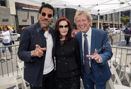 Television producer Nigel Lythgoe, right, is joined by Lionel Richie, left, and Priscilla Presley at a ceremony honoring him with a star on the Hollywood Walk of Fame on his 72nd birthday, in Los Angeles. The ceremony was initially scheduled for April 1, 2020, but was postponed due to the coronavirus outbreak