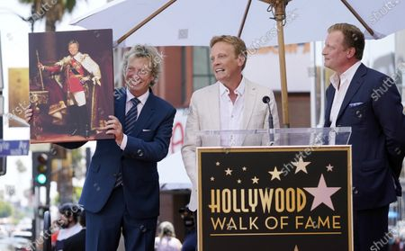 """Stock Picture of Television producer Nigel Lythgoe, left, poses with a mock painting entitled """"King Nigel"""" from his sons Simon, center, and Kristopher at a ceremony honoring him with a star on the Hollywood Walk of Fame on his birthday, in Los Angeles. The ceremony was initially scheduled for April 1, 2020, but was postponed due to the coronavirus outbreak"""