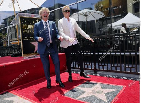 Television producer Nigel Lythgoe, left, and his son Simon dance together at a ceremony honoring him with a star on the Hollywood Walk of Fame on his 72nd birthday, in Los Angeles. The ceremony was initially scheduled for April 1, 2020, but was postponed due to the coronavirus outbreak
