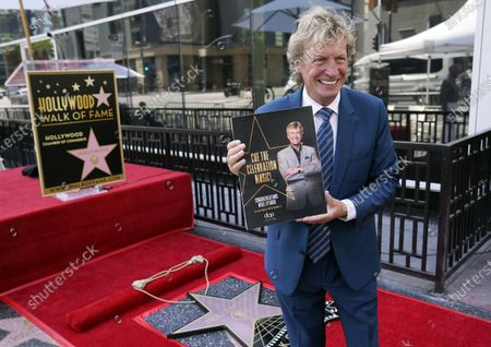Television producer Nigel Lythgoe poses with a program before a ceremony honoring him with a star on the Hollywood Walk of Fame on his 72nd birthday, in Los Angeles. The ceremony was initially scheduled for April 1, 2020, but was postponed due to the coronavirus outbreak