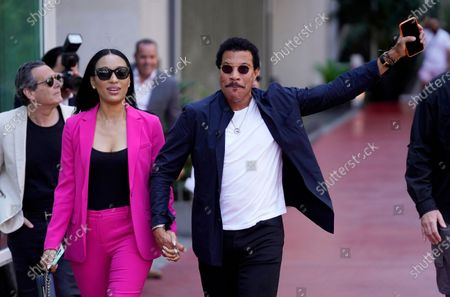Singer Lionel Richie, right, arrives with his girlfriend Lisa Parigi at a ceremony honoring television producer Nigel Lythgoe with a star on the Hollywood Walk of Fame, in Los Angeles. The ceremony was initially scheduled for April 1, 2020, but was postponed due to the coronavirus outbreak