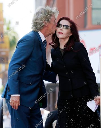 Television producer Nigel Lythgoe, left, kisses Priscilla Presley before she spoke at a ceremony honoring him with a star on the Hollywood Walk of Fame on his 72nd birthday, in Los Angeles. The ceremony was initially scheduled for April 1, 2020, but was postponed due to the coronavirus outbreak