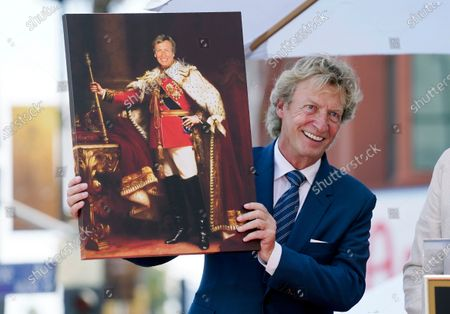 """Television producer Nigel Lythgoe poses with a mock portrait of him entitled """"King Nigel"""" from his sons Simon and Kristopher at a ceremony honoring him with a Hollywood Walk of Fame star on his 72nd birthday, in Los Angeles. The ceremony was initially scheduled for April 1, 2020, but was postponed due to the coronavirus outbreak"""