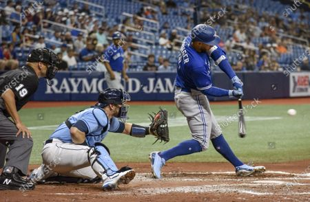 Stock Image of Umpire Vic Carapazza, left, and Tampa Bay Rays catcher Mike Zunino, center, look as Toronto Blue Jays' George Springer hits an RBI-single to center field during the third inning of a baseball game, in St. Petersburg, Fla