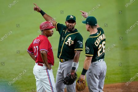 Texas Rangers third base coach Tony Beasley looks to the dugout as Oakland Athletics' Elvis Andrus, center, and Matt Chapman (26) talk about a ball hit by the Rangers' Eli White during the third inning of a baseball game in Arlington, Texas