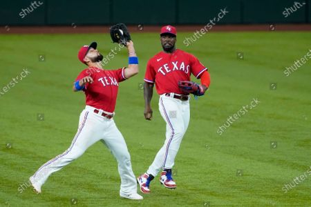 Texas Rangers shortstop Isiah Kiner-Falefa catches a fly ball hit by Oakland Athletics' Matt Chapman as center fielder Adolis Garcia, right, moves to avoid a collision during the fourth inning of a baseball game in Arlington, Texas