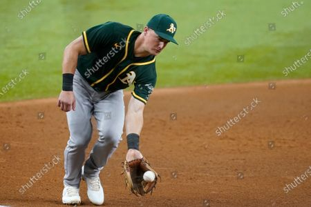Oakland Athletics third baseman Matt Chapman reaches down to field a grounder by Texas Rangers' John Hicks, who was out at first during the fifth inning of a baseball game in Arlington, Texas