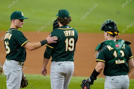 Oakland Athletics' Matt Chapman, left, and catcher Sean Murphy (12) stand by starting pitcher Cole Irvin (19), who waits on the mound to be pulled during the sixth inning of the team's baseball game against the Texas Rangers in Arlington, Texas