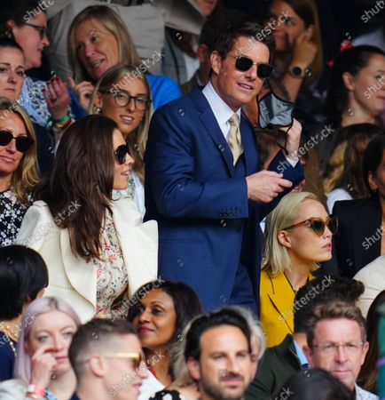 Hayley Atwell, Tom Cruise (taking off his facemask) and Pom Klementieff watching the action on Centre Court during the Ladies' Singles final