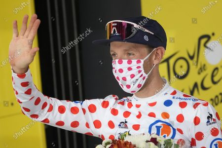 Michael Woods of Canada, wearing the best climber's dotted jersey, celebrates on the podium after the fourteenth stage of the Tour de France cycling race over 183.7 kilometers (114.1 miles) with start in Carcassonne and finish in Quillan, France