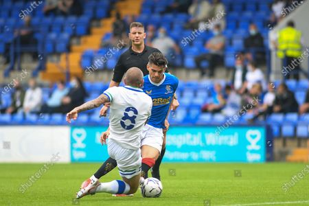 Tranmere Rovers midfielder Jay Spearing (8) makes a slide tackle against Ranger's FC midfielder Ianis Hagi (7) during the Pre-Season Friendly match between Tranmere Rovers and Rangers at Prenton Park, Birkenhead