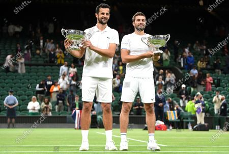 Croatian players Mate Pavic (L) and Nikola Mektic (R) pose with their trophies after winning their men's doubles final against Marcel Granollers of Spain and Horacio Zeballos of Argentina at the Wimbledon Championships in Wimbledon, Britain, 10 July 2021.