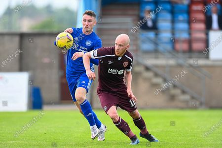 Stock Image of Andrew McDonald (#4) of Peterhead FC and Liam Boyce (#10) of Heart of Midlothian FC tussle for the ball during the Premier Sports Scottish League Cup match between Peterhead FC and Heart of Midlothian FC at Balmoor, Peterhead