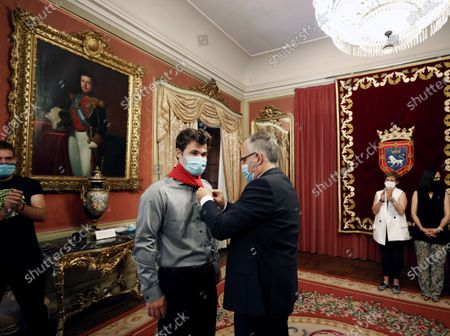 Pamplona's Mayor, Enrique Maya (R), puts on a traditional St. Fermin red bandana to Norwegian chess master Magnus Carlsen (L), who received the 'Premio Guri del Ano' award, during the San Fermin Mundial chess festival held in Pamplona, Navarra, Spain, 10 July 2021.
