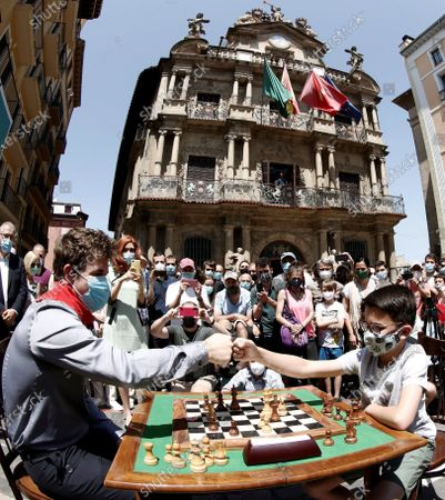 Norwegian chess master Magnus Carlsen (L), who received the 'Premio Guri del Ano' award, plays a game against Spain's U12 chess champion, Javier Habans Aguerrea (R), during the San Fermin Mundial chess festival held in Pamplona, Navarra, Spain, 10 July 2021.