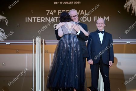 Festival director Thierry Fremaux, center, embraces Isabelle Adjani as festival president Pierre Lescure, right, looks on at the premiere of the film 'Peaceful' at the 74th international film festival, Cannes, southern France
