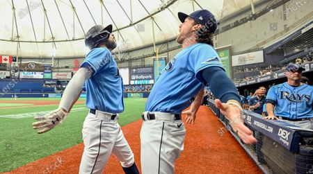 Tampa Bay Rays' Brett Phillips celebrates with Brandon Lowe, left, after Lowe's solo home run off Toronto Blue Jays starter Ross Stripling during the first inning of a baseball game, in St. Petersburg, Fla