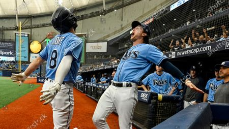 Tampa Bay Rays' Brett Phillips, center, steps out of the dugout to celebrate with Brandon Lowe (8) after his solo home run off Toronto Blue Jays starter Ross Stripling during the third inning of a baseball game, in St. Petersburg, Fla