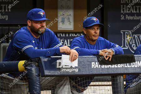 Toronto Blue Jays coach John Schneider, left, and manager Charlie Montoyo watch from the dugout during the eighth inning of a baseball game against the Tampa Bay Rays, in St. Petersburg, Fla