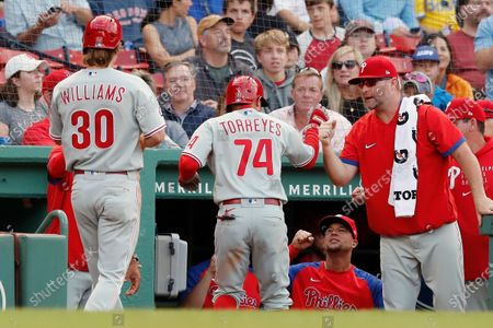 Philadelphia Phillies' Ronald Torreyes (74) and Luke Williams (30) celebrate after scoring on a single by Jean Segura during the eighth inning of a baseball game against the Boston Red Sox, in Boston