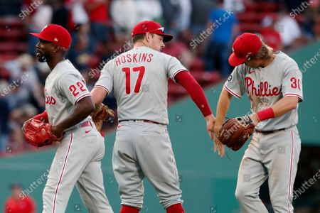 Philadelphia Phillies' Rhys Hoskins (17), Andrew McCutchen (22) and Luke Williams (30) celebrate after defeating the Boston Red Sox in a baseball game, in Boston