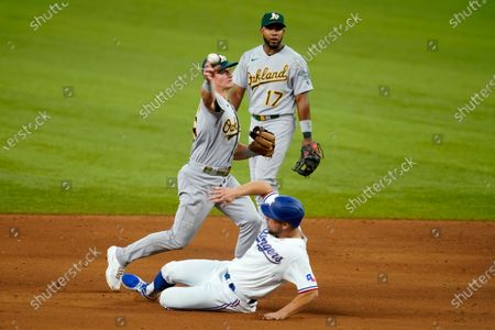Oakland Athletics third baseman Matt Chapman, top left, throws to first to complete the double play after forcing out Texas Rangers' Nate Lowe, bottom, at second as shortstop Elvis Andrus, top right, looks on in the fifth inning of a baseball game in Arlington, Texas, . The Rangers' Joey Gallo was out at first on the play