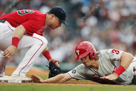 Boston Red Sox's Bobby Dalbec (29) misses the pickoff attempt at first base on Philadelphia Phillies' Luke Williams during the sixth inning of a baseball game, in Boston