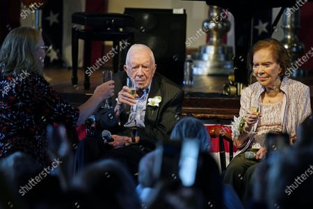 Amy Carter, left, rises her glass during a toast to her parents former President Jimmy Carter and former First Lady Rosalynn Carter during a reception to celebrate their 75th wedding anniversary, in Plains, Ga